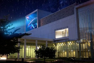A rendering of the Moss Arts Center shows a colorful projection on display on the side of the building.
