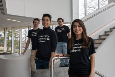 The University Innovation Fellows - four students wearing black t-shirts posing at the bottom of a staircase.