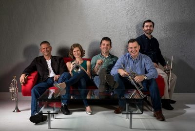Five trumpet players, four men and one woman, sit on a red sofa holding their instruments.