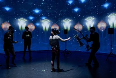 Researchers dressed in black hold various props as a user navigates the dark space decorated with colorful and unusual shapes.